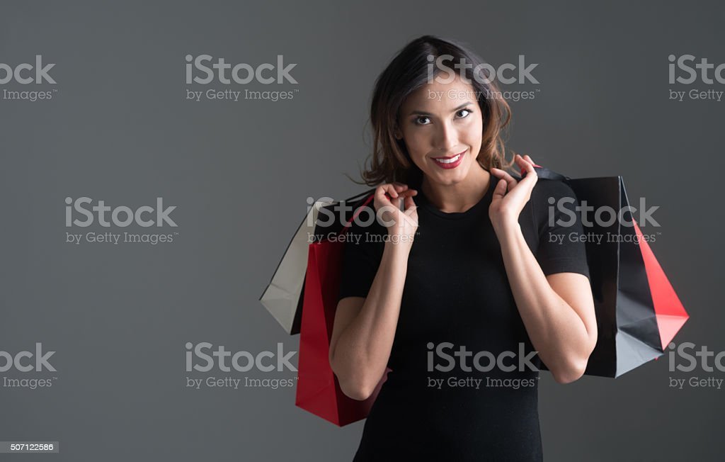 Elegant Asian shopping woman holding bags and looking at the camera -...