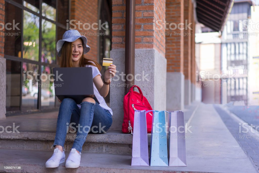 Asian shopping woman using credit or debit card and laptop for online...