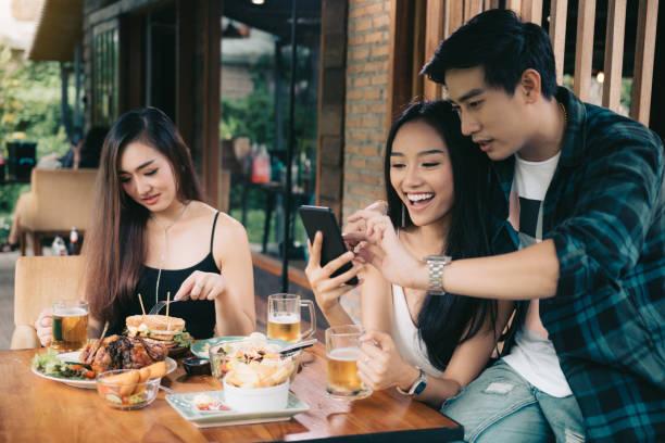 Femme célibataire asiatique envieux avec le couple d'amour faisant prendre selfie au restaurant. - Photo