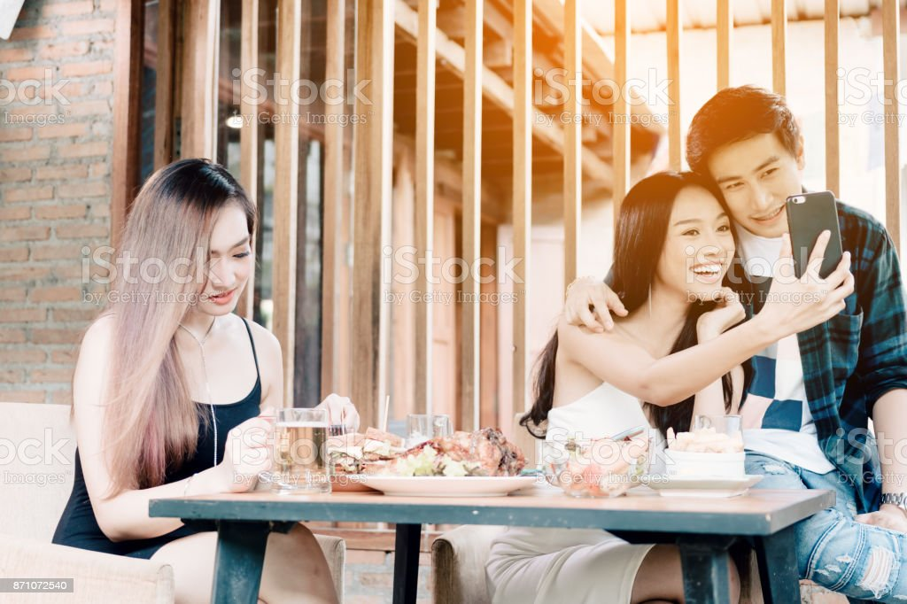 Asian single woman envious with love couple doing take selfie at restaurant. stock photo