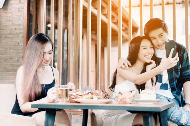 Asiatique femme célibataire envieuse avec amour couple faisant prendre selfie au restaurant. - Photo