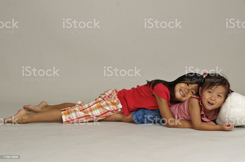 Asian sisters laying on floor royalty-free stock photo