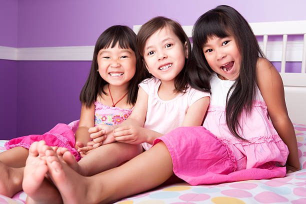 asiatischen schwestern porträt - lila mädchen zimmer stock-fotos und bilder