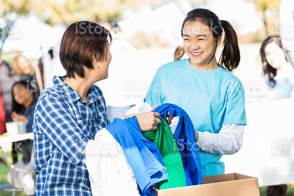 Asian sisters sorting clothing donations together at charity drive royalty-free stock photo