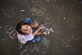 Asian small girl with chalk on painted asphalt background above top view