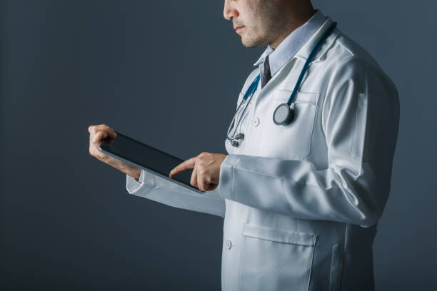 Asian smart doctor holding and touch tablet computer with hand. Surgeon has stethoscopes. concept of medical, technology, information and big data. stock photo