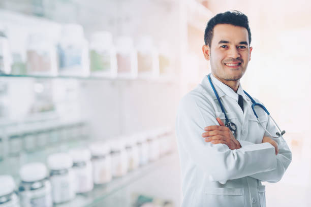 Asian smart doctor standing arms crossed and carrying stethoscope on shoulders at hospital with blurred drugstore background, concept of business advertising and consultation treatment patient. stock photo