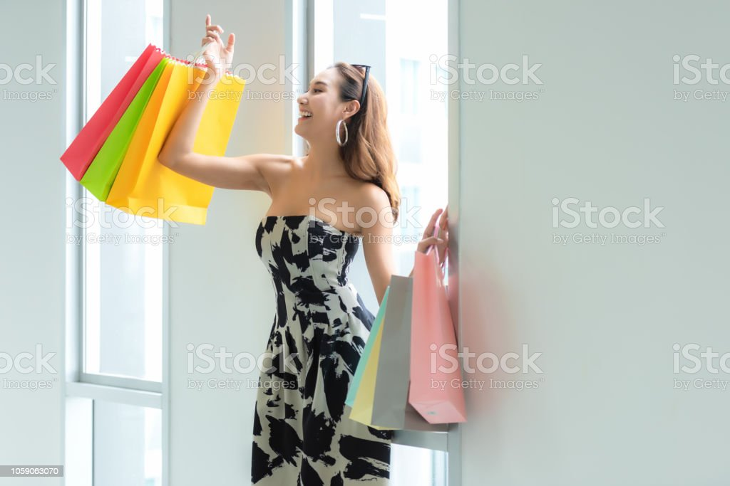 Asian smiling woman so happy shopping online with her shopping in...