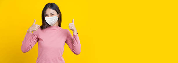 Asian smiling woman wearing mask and thumb up action to be grad, banner or showing on isolated yellow color background, Coronavirus pandemic, covid19 outbreak, banner and beauty with covid19 protect