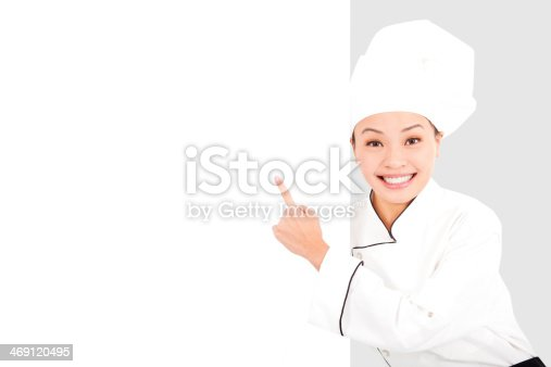 istock Asian smiling  young woman chef pointing  with blank board 469120495