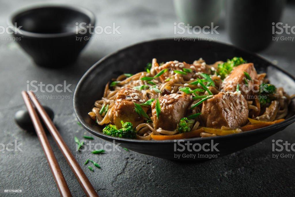 Asia soba tallarines y teriyaki salmón en tazón de fuente negro - foto de stock