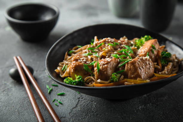asian soba noodle and teriyaki salmon  in black bowl - chinese food stock photos and pictures