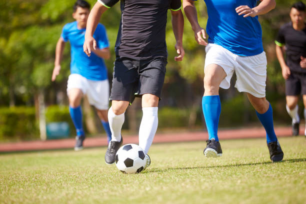 asian soccer football player playing outdoors stock photo