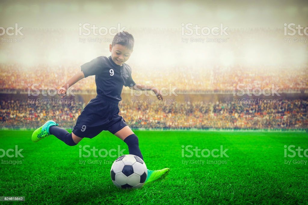 asian soccer kid kicking football in the stadium stock photo