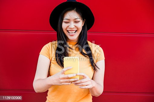 535970955 istock photo Asian social influencer woman using smartphone - Happy chinese girl having fun with new trends technology - Fashion, tech and millennial generation activity - Focus on face 1129132000
