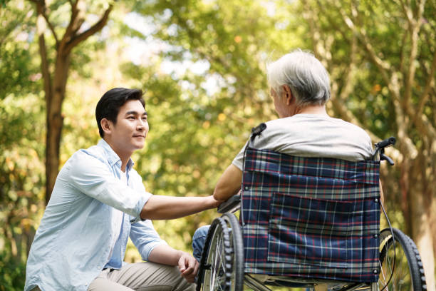 asian son consoling wheelchair bound father outdoors stock photo