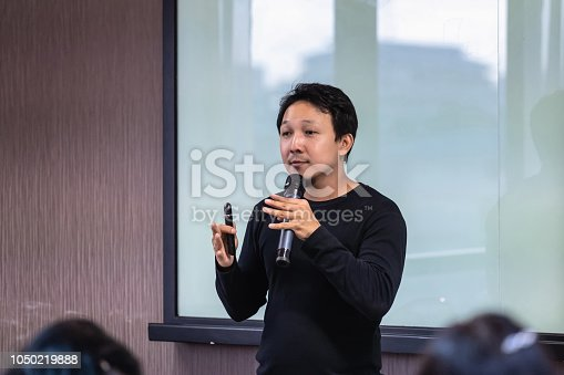 1158085965 istock photo Asian Speaker or lecture with casual suit on the stage in front of the room presenting with the screen in the conference hall or seminar meeting room, business and education concept 1050219888