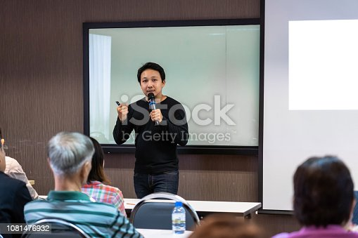 1158085965 istock photo Asian Speaker or lecture with casual suit on the stage in front of the room presenting with the screen in the conference hall or seminar meeting room, business and education concept 1081476932