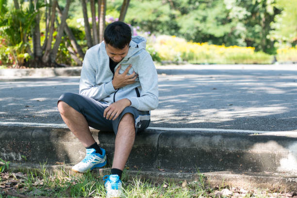 asiatische sportler mit schmerzen in der brust setzte sich nach der ausführung im park der verletzung der übung konzept - herz lungen training stock-fotos und bilder