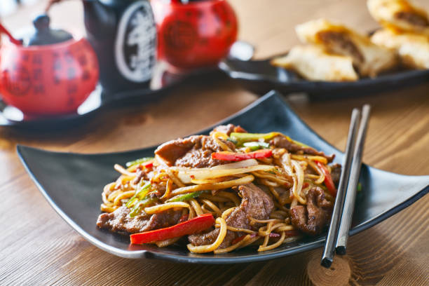 asian stir fried noodles with beef peppers and onions stock photo