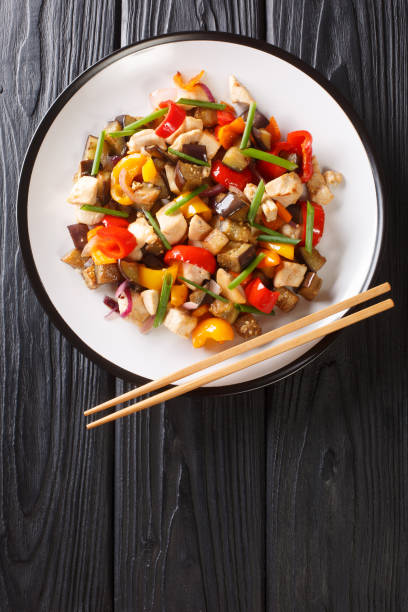 Asian stir fry chicken with eggplant, pepper and onion close-up in a plate. vertical top view stock photo