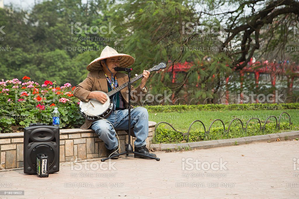 Asian street musician troubadour performing a folk song stock photo