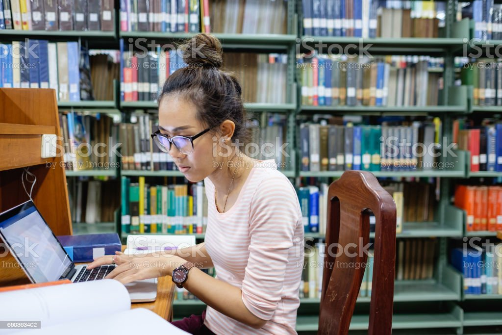 Asian student concentrating on study in library stock photo