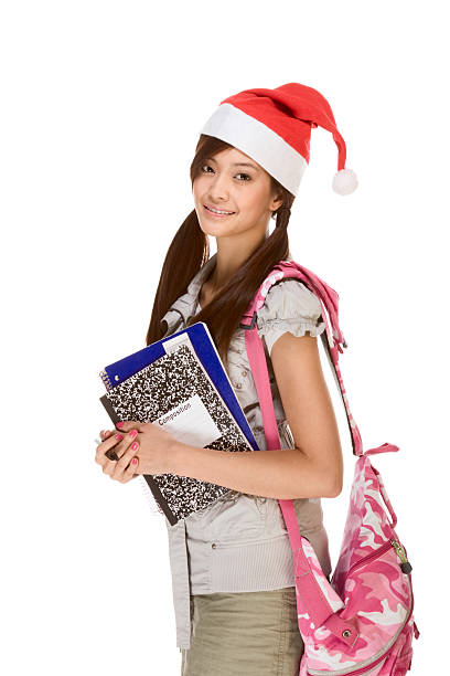 Asian student girl in Christmas Santa hat with composition book stock photo