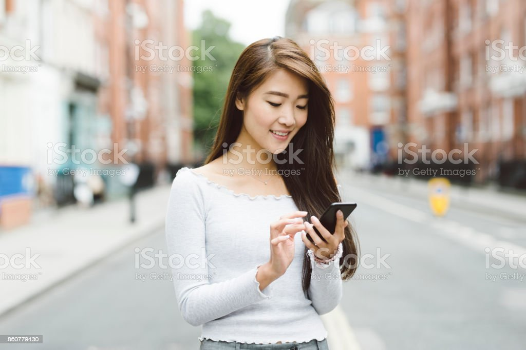 Asian Student in London Using Smart Phone stock photo