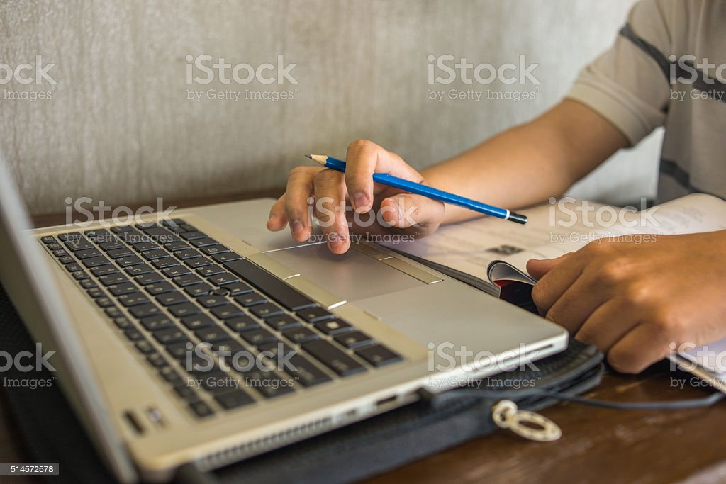 Asian student searching information on the Internet and reading book stock photo