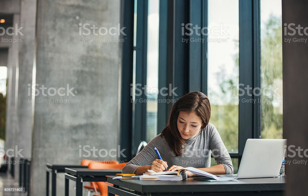 Asian student studying in library - foto stock