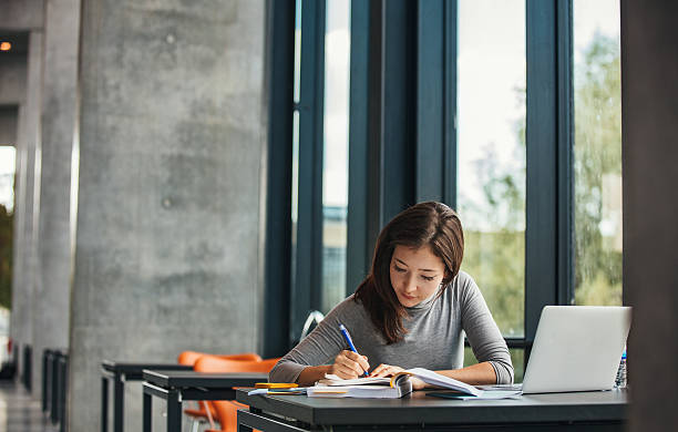 Asian student studying in library stock photo