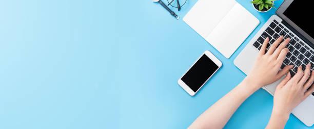 gli studenti asiatici navigano su internet per la ricerca di lavoro. scrittore di blog freelancer digitando isolato su un concetto minimo di scrivania blu pulito, spazio di lavoro, spazio di copia, lay piatto, vista dall'alto, mock up - flat lay foto e immagini stock