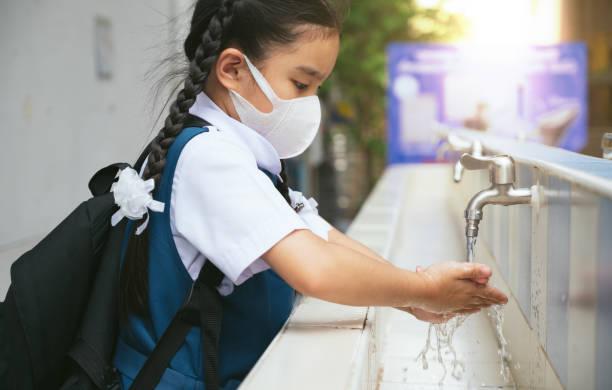 Asiatische Schüler waschen Hände am Außenwaschbecken in der Schule. Prävention ansteckender Krankheiten, Pest. Kinder Gesundheit, Schutz des Virus Covid - 19 , Wasser sparen, Reinigung, fließendes Wasser. – Foto