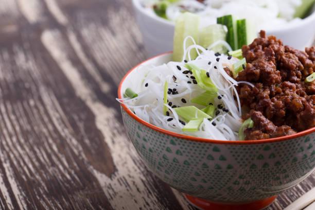 Asiatische Schüssel mit gemahlenen Rindfleisch, Reisnudeln, Gurken, grünen Zwiebeln und Sesamsamen – Foto