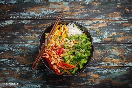 Asian, Chinese or Vietnamese style noodles salad with fresh vegetables, fried tofu and peanuts, served in rustic ceramic bowl on colorful wooden background. Healthy diet clean eating or vegan concept