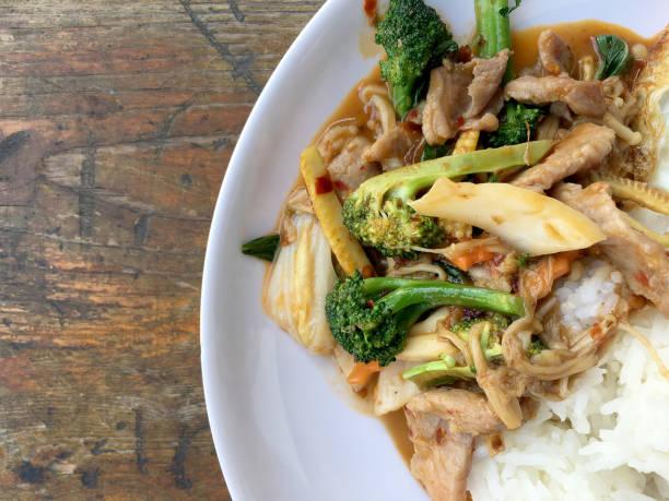 Estilo asiático salteado con trozos de carne con vegetales frescos con arroz y huevos fritos estilo tailandés situado en plato blanco sobre mesa de madera. - foto de stock