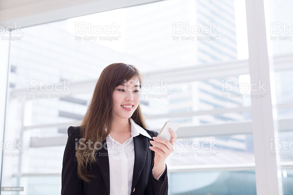 asian successful businesswoman using smart phone at office corridor royalty-free stock photo