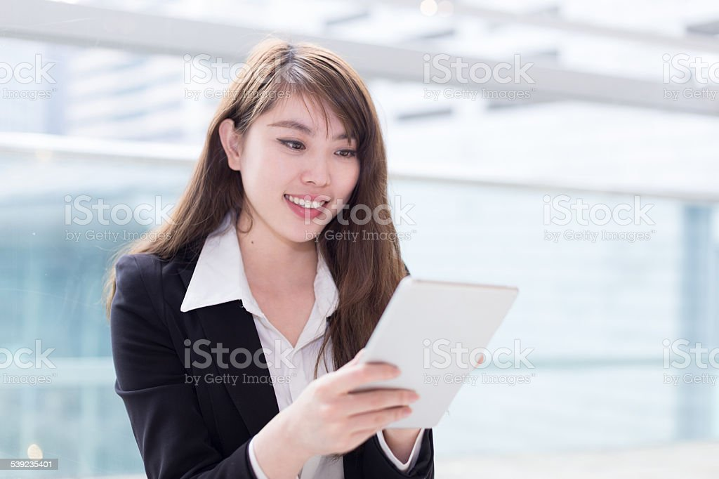 asian successful  businesswoman using tablet in office corridor royalty-free stock photo