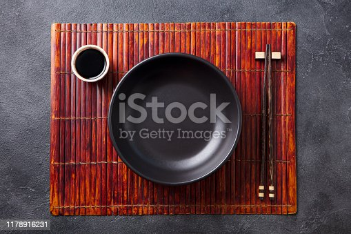 Asian table place setting with bamboo placemat, sauce bowl and chopsticks. Top view. Copy space