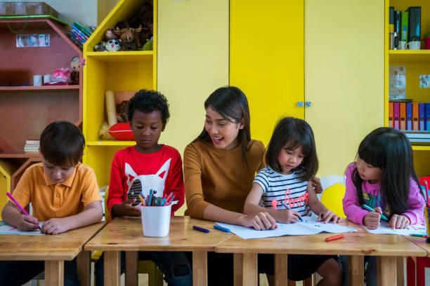 asian teacher and student in an international preschool study art subject togather - preschool teacher stock pictures, royalty-free photos & images