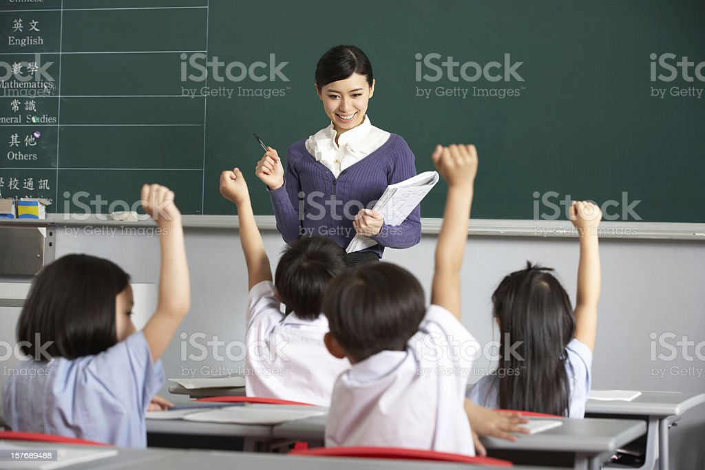 Asian Teacher And Students In Classroom With Arms Raised -3044