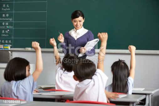 181085327 istock photo Asian teacher and students in classroom with arms raised 157689488