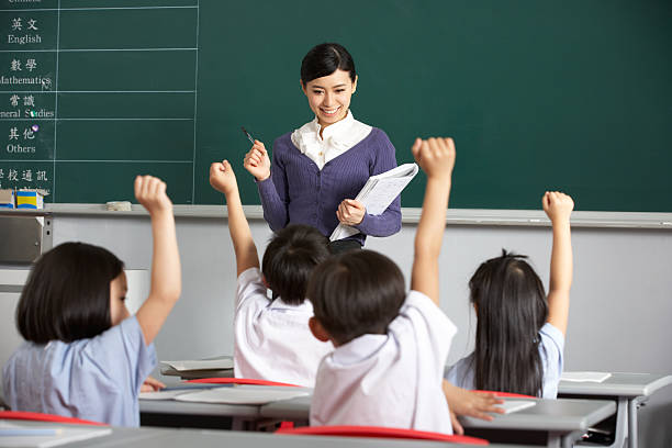 Asian teacher and students in classroom with arms raised stock photo