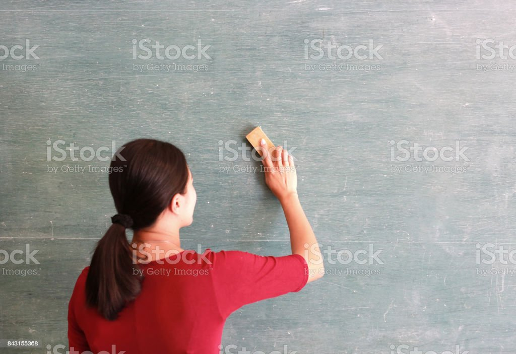 asian teacher erases on blackboard with board eraser in classroom, Education concept. stock photo