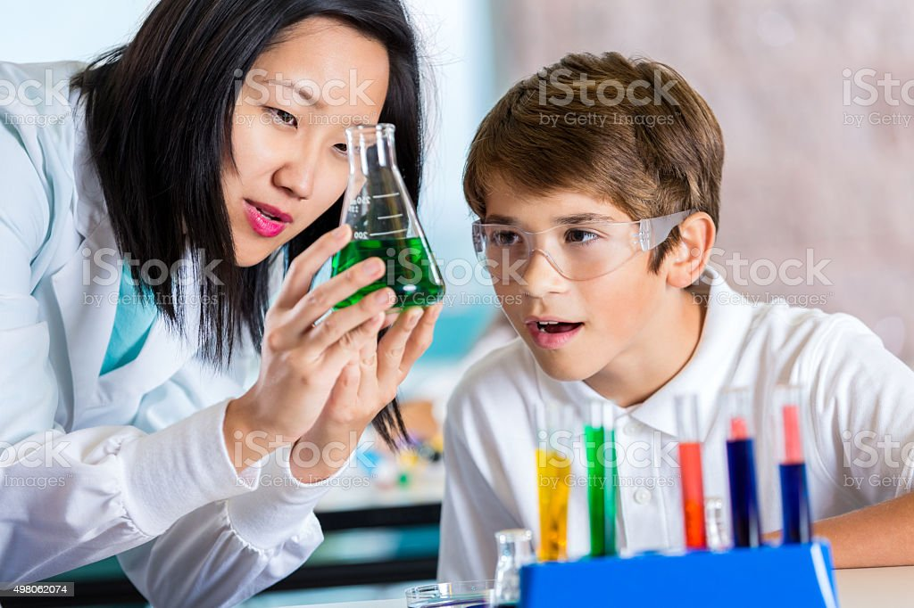 Asian teacher helping preteen student with chemistry experiment stock photo