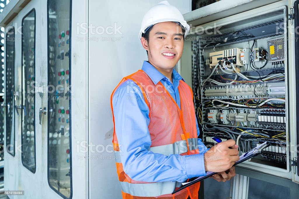 asian technician at panel on construction site royalty free stock photo