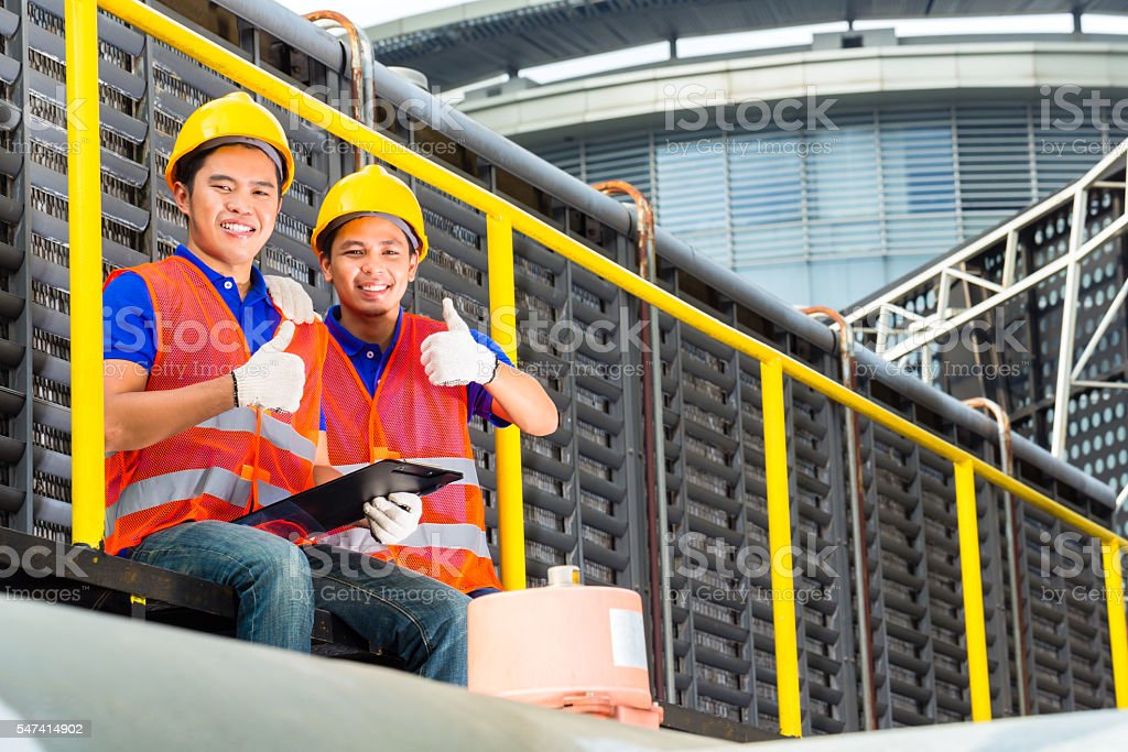 Asian technicians or workers on construction site stock photo