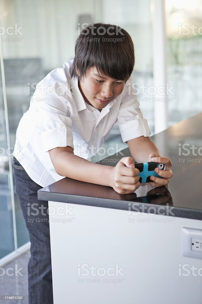 Asian teenage boy playing video game royalty-free stock photo