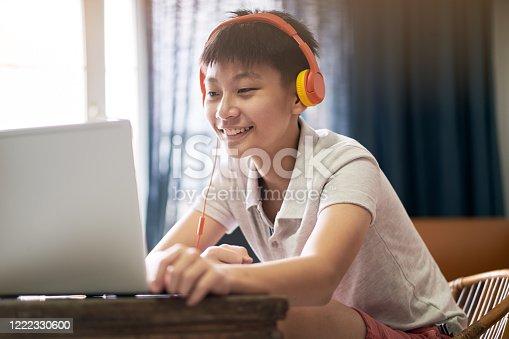 Asian teenage boy studying at home wearing headset & smiling